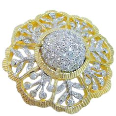 Netti Rosenstein's 1950's sparkling white rhinestone gold plate floral brooch could pass for the real thing. Its a real dazzler with a 'pie crust' gold plated border design that has sections with rhodium plated flower cut-outs resembling cut-work lace & pave set rhinestones and then a high dome pave-set cabochon prong set in the center!