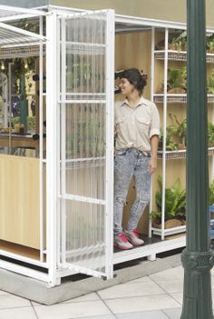 """Located in the rooftop of Buenos Design center (Recoleta). This """"pop-up box"""", called the """"Camping's shelter """", works with the green  and nature that surround it. The translucent  facade and the thin white metal structure,   was designed to fold itself  and open entirely, working  as a light  filter that contains plants and all the functions for the store. During the night, this space look like a lantern in the rooftop, transparent, lighting and green ."""
