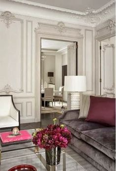 Lush gray velvet sofa, burgundy accent pillows and florals, white club chair, modern lamp, and crown moldings... Sheer romance. Paris.