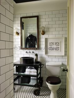 A washstand on wheels, two metal lamp sconces, and the functional white tiled walls give this bathroom an industrial feel