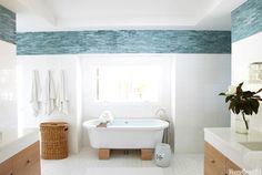 Para imitar el océano fuera de este cuarto de baño Laguna Beach, diseñadores Heidi Bonesteel y Michele trucha añadido una frontera de azulejo azul turquesa.  Debajo de ella, las paredes están acabados con azulejos pies cuadrados, que dan a la habitación un aspecto como en un balneario limpio porque hay menos líneas de la lechada.