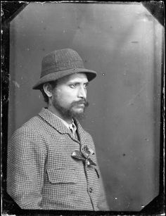 Half length studio portrait of an unidentified Maori man, photographed by William James Harding of Wanganui between 1856 to 1889. He has a beard and a moustache. He wears a jacket decorated with a camelia flower, and a hat
