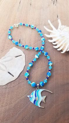 Angelfish Fish Blue Stone Beaded Pendant Necklace Ocean Jewelry. 100% handmade, one-of-a-kind necklace.  This gorgeous handmade necklace is made of dark blue faceted beads, various blue stone beads, and various silver spacer beads. The necklace focal point is a blue striped angelfish pendant. The necklace is finished with a silver toned lobster claw clasp.  Please note, as with all stones, beads and pendants may have minor imperfections and discolorations making them each unique to the…