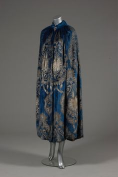 A Maria Gallenga stencilled velvet evening cape, 1920s, the royal blue velvet ground with silver and gold Renaissance style pomegranite motifs, lined in pale green satin, padded collar with Murano glass beads to fasten.