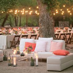 Set just beyond the dinner table and in front of the outdoor dance floor was this modern white lounge. Clear coffee tables filled with candl...