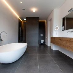 Eine freistehende #Badewanne im Ei-Design bringt in den sonst sehr klar und kantig strukturierten Raum mehr Leben und Bewegung.