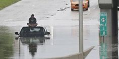 A stranded motorist sits on top his car as he awaits rescue from the flooded Southfield Freeway, Monday, Aug. 11, 2014, in Dearborn, Mich. The Michigan State Police issued an advisory Monday evening, urging drivers to avoid non-essential use of all metro Detroit freeways after heavy rain and thunderstorms left roads flooded and impassable. Interstate 75 at I-94 in Detroit has been shut down in both directions, according to the Michigan Department of Transportation.