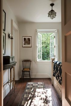 FAB hallway. Two things that stand out: That amazing floor and the narrowest of the narrow tri-legged tables...super cute! Great classic wood door and good colors. Love.