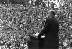 Clark Kerr was UC Berkeley's first chancellor. This picture shows Kerr leading a meeting in the Greek Theater at the University of California, Berkeley. Kerr liberalized certain features of campus governance while overseeing increasingly strict regulation of key activities - essentially thrusting student activism off-campus just as its energies were rising. During this speech, Mario Savio was taken away because he attempted to address the audience at the end of the meeting.