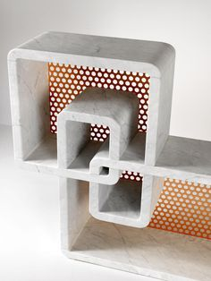 sculptural shelving made of Carrara marble, perforated metal sheets, and copper and brass