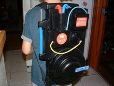 Ghostbusters Proton Pack, my husband created something similar. Brown craft boxes (large and small rectangles and circles), duct tape, black spray paint...