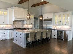 White inset cabinets with a dark wood floor, decorative wood hood, large gray island, wolf range, subzero refrigerator, wooden beams, vaulted ceiling, double doors with glass at the top, furniture toes, staggered Heights, and a marble backsplash.