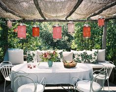 Something about a brightly colored paper lantern instantly telegraphs a festive mood. Here, pillows in leafy prints echo the verdant landscape.