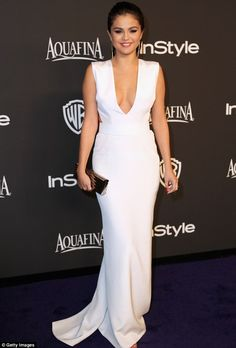 A wonder in white: The 22-year-old singer and actress showed off her figure in the deep V-cut frock featuring cutouts on the side as she accessorised with a metallic silver clutch