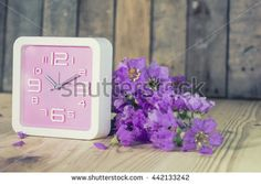 Bright pink  wall clock on a wooden table. Style Vintage. - stock photo
