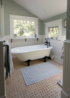 On the second floor, the remodeled master bathroom features a claw tub under a skylight. The airy space has white bead board molding and a beige tiled floor.