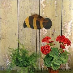 """Charming wooden Bee Garden Stake with a metal pole 36"""" high. Bumble bee has wire antennas and metal screening for wings. Measures 10.5"""" long."""