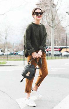 Street style look com suéter verde, calça marrom e tênis branco.