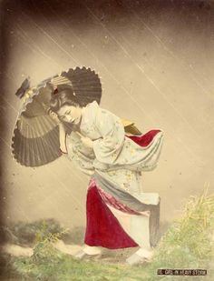 by Kusakabe Kimbei, ca. 1880 (This 'Girl in heavy storm', attributed to Kusakabe Kimbei, is one of the most spectacular images of 19th c. Japanese photography, colored according to the aesthetics of ukiyo-e prints, and where it was also create a sense of ultimate realism. Photographer simulated the effect of the negative streaking rain, wind and printing was achieved by introducing rods in kimono model, seeking an illusionism that refers both to the engraving and the world of kabuki theater)