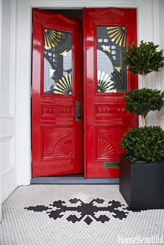 Reviving an Early American symbol of welcome, Fulk painted the front doors Benjamin Moore Heritage Red. He echoed existing carved-fan motifs in new gilt stencils on the glass.