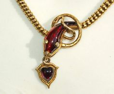 The fashion for serpent motif jewellery was inspired by Queen Victoria's own serpent jewels. This fine quality example, circa 1840, is in high-carat gold, the articulated links suggesting the texture of snakeskin. The head is set with a domed, carved, carbuncle garnet, with rose-cut diamond eyes and nose. A garnet heart locket, similarly set, hangs from its mouth.The tongue of the clasp enters the side of the serpent's head, forming a V. This made it attractive when worn on the high…