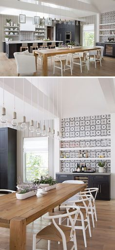 The dining area in this farmhouse inspired house, has a large 8 person wood dining table surrounded by white chairs. Simple light bulbs hang above the dining table, helping to anchor the dining table in the open floor plan, and beside the dining table is a bar area with white floating shelves and decorative tiles. These floating shelves and decorative tiles are also used in the kitchen, creating a cohesive look for the space. #DiningRoom #Kitchen
