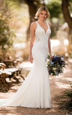 This beach wedding gown with sheer side cutouts from Essense of Australia is anything but ordinary with lace and crepe fabric and a sleek column silhouette.