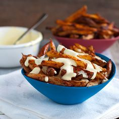 These baked spicy fries use egg whites to get the fries crispy and golden on the outside. Topped with a lighter garlic cheese sauce. | pinchofyum.com