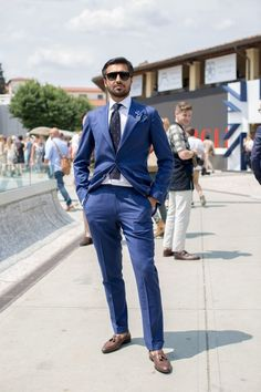 A blue suit and a white dress shirt will showcase your sartorial self. Brown leather tassel loafers will contrast beautifully against the rest of the look.   Shop this look on Lookastic: https://lookastic.com/men/looks/suit-dress-shirt-tassel-loafers-tie-pocket-square-lapel-pin-sunglasses/13138   — Black Sunglasses  — Blue Lapel Pin  — Blue Plaid Pocket Square  — Navy and White Polka Dot Wool Tie  — White Dress Shirt  — Blue Suit  — Brown Leather Tassel Loafers