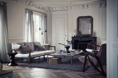 A traditional Haussmannian interior, updated with a moody, gray palette and plush textiles by designer Bertrand Benoit.
