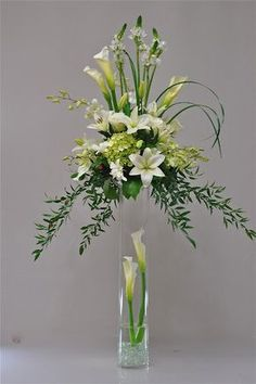 Tall, green and white centerpiece with calla lilies                                                                                                                                                      More