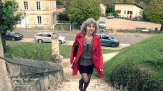 Femme en rouge qui monte un escalier. Vue du village en plongée.