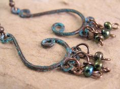 Beautiful hand aged copper chandelier earrings featuring dangling hand picked metallic seed beads in iridescent shades of  green.I hand aged these copper pieces using my own special technique which gives them a wonderful old world look These earrings match this pendant necklace: http://www.zibbet.com/TheAmethystDragonfly/artwork