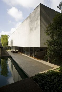Casa Patio - Marcio Kogan. white blank rendered wall. minimal patio courtyard and swimming pool. reflection pond. hovering mass