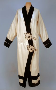 LADY'S WOOL and VELVET COAT, c. 1912. Cream felt kimono style trimmed in black velvet with cream piping, having two large corded leaf form appliques and corded button and loop closures, back decorated with two rows of buttons lined in cream satin with ribbon binding. B-44, L-54. SM. (Lining split, needs cleaning) good