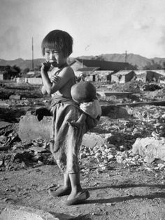 Girl Standing in Rubble from the Korean Civil War, Carrying a Baby in a Sling on Her Back Premium Photographic Print by Joe Scherschel at http://Art.com