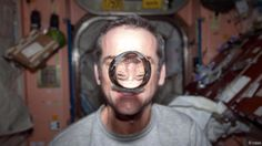 Hadfield watches a water bubble float freely between him and the camera (Credit: NASA) BBC