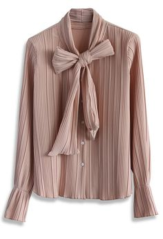 """Nothing says """"graceful"""" and """"chic"""" like a pleated pussy bow top! The stretchy fabric offers a lovely texture to the top while the slight bell sleeves and pussy bow complete the garment with elegance. Dress this navy top up with a trusty pencil skirt or down with denim!"""