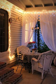 back porch with drapes and lights. Also notice the trellis. Looks so cozy. Love it!