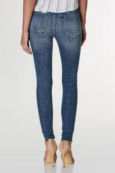 Classic mid rise skinny jeans with dark vintage style wash and subtle distressing. Asymmetrical raw hem finish with five pocket design and button, zip closure.    Cotton-Spandex blend  Imported  Model is wearing size 3  Runs true to size  Machine wash cold