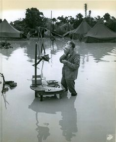"""Okinawa, 28 May 1945 by Marine Corps Archives & Special Collections, via Flickr. The caption on this photograph reads """"Indifferent-Completely ignoring that fact that his camp is half submerged by heavy Okinawa rains, Marine Staff Sergeant A.S. Barnacle, of Minneapolis, Minn., stands knee deep in water to shave at his """"Rube Goldberg"""" washstand."""" From the Photograph Collection (COLL/3948), Marine Corps Archives & Special Collections OFFICIAL USMC PHOTOGRAPH"""