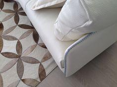 Into the mix.wood tile,cowhide rug and white leather sofa. Studiohugomijares.com