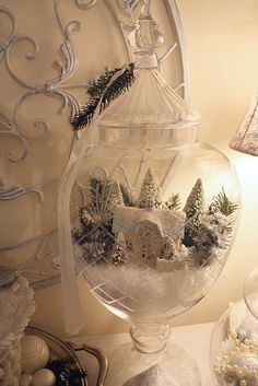 Fill a large apothecary jar with plastic snow and put a small cottage ornament on top and decorate it with trees and more snow. Pretty DIY for the holidays!