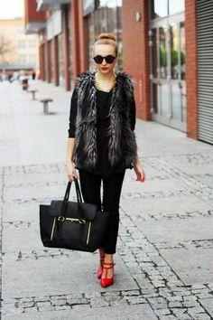 Outfit in Schwarz mit Fellweste und roten Schuhen