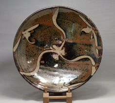 sig1618 Large stoneware dish with kaki over tenmoku glaze and wax resist pattern. Sold with orginial individually made wooden box. £5,000