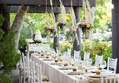 { This embodies everything that I would expect out of a shabby chic, daytime wedding! I love the lanterns and the ribbon. You don't need a centerpiece if you are hanging chandeliers/bird cages/lanterns from up above...Oh and look in the background! It's a cake on a piece of furniture! Love this. }