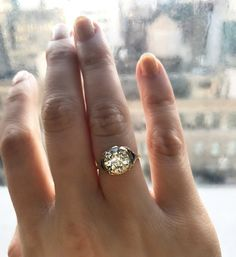 The Astor ring is a Vintage Engagement Ring with the diamond circa 1920 and the setting circa 1950! The ring centers and incredible old European cut diamond weighing 2.29 carats of L-M color, VS2 clarity. The diamond is held by four 14kt yellow gold prongs. To each side of the diamond is a bezel-set triangular cut blue  sapphire . The gallery contains a bezel set round cut diamond on each side surrounded by open metal work designs. The ring is size 5.5 and can be resized!