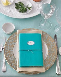 If you plan to ask guests to read from the Haggadah, consider incorporating the book of prayers and stories into every setting. We covered each book in a sheet of decorative paper and a layer of blue vellum to coordinate with the dishes. Then, we used silk cord to bundle it with the napkin. Self-adhesive labels let the books double as place cards