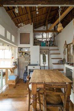アトリエからの日差しが届くダイニング。テーブルとイスはアンティーク。階段の上は屋根裏部屋に。