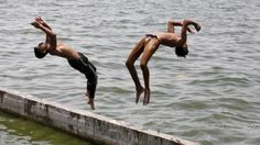 Two boys jump into the waters of the Sabarmati River to cool off themselves on a hot summer day in Ahmedabad, India as temperatures continue to eclipse 40 degrees Celcius. About Climate Change, Beat The Heat, Feature Film, Summer Days, Beats, Around The Worlds, River, City, People